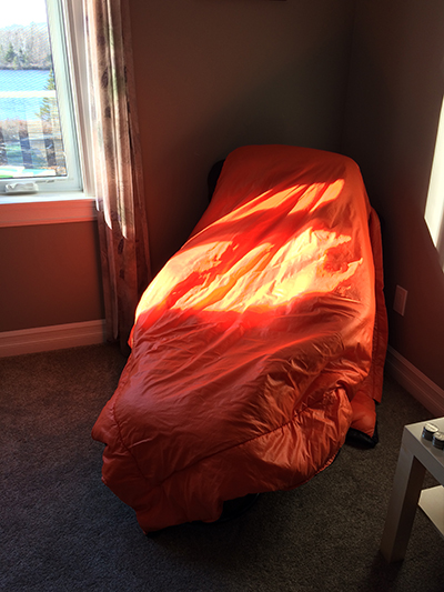 On the chair, under the sleeping bag, in the sun